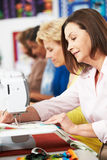 Group Of Women Using Electric Sewing Machines In class Stock Image