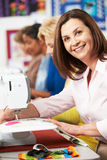 Group Of Women Using Electric Sewing Machines In class Stock Photo