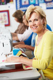 Group Of Women Using Electric Sewing Machines In class Stock Photos