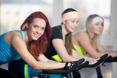 Group of women working out on cycles Stock Photography