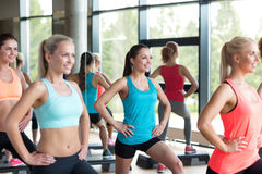 Group of women working out with steppers in gym Stock Photos