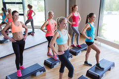 Group of women working out with steppers in gym Stock Photo
