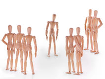 Group of wooden dummy characters standing around one royalty free stock image