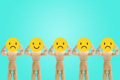 Group of wooden figure standing and holding face emotions in sadness and happiness. Group of wooden figure mannequin standing and holding face emotions in royalty free stock photography