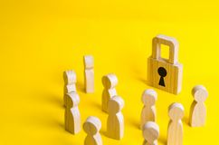 A group of wooden figures of people surround and look at the padlock. The concept of protecting personal data in social networks. royalty free stock image
