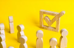 A group of wooden figures of people surround and look at a tick in the box. Voters take part in elections. Voting, referendum, soc. Ial survey. Statistical data Stock Photos