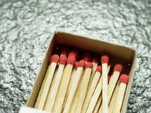 A group of wooden match sticks with red head in match box over black or dark granite texture. With concepts of energy, old fashion, vintage, and retro Royalty Free Stock Photography