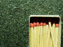 A group of wooden match sticks with red head in match box over black or dark granite texture. With concepts of energy, old fashion, vintage, and retro Royalty Free Stock Photo