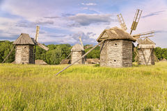 Group of wooden windmills in a meadow royalty free stock images