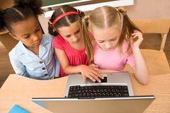 Group work. Above angle of three schoolgirls looking at the laptop during lesson Stock Images