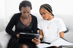Group work. These two women share the knowledge by working together on a laptop Royalty Free Stock Images
