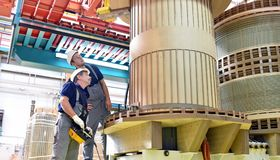 Group worker assembles a transformer in mechanical engineering -. Teamwork at work stock image