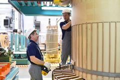 Group worker assembles a transformer in mechanical engineering -. Teamwork at work stock photo