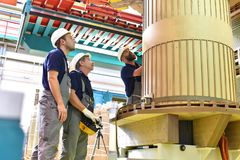 Group worker assembles a transformer in mechanical engineering -. Teamwork at work royalty free stock image