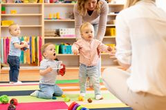 Group of workers with babies in nursery. Or kindergarten royalty free stock photos