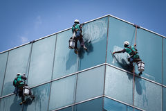 Group of workers cleaning windows service on high rise building. For any use stock photo