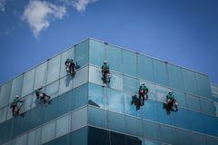 Group of workers cleaning windows service on high rise building Stock Photography