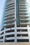 Industrial climber wash the windows of modern skyscraper. Dubai UAE. royalty free stock images
