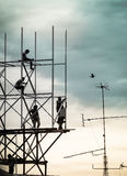 Group of workers are climbing poles to install billboards Stock Images