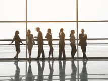 Group of workers communicating in business center. Full length of men and women standing and talking to each other while waiting for conference in hall Stock Images