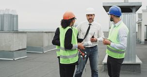 Group of workers in a construction site engineer architect businessmen have a meeting on the rooftop of construction