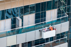 Group of workers in cradle inspecting facade of skyscraper. Building with aluminium panels facade inspection and maintenance Royalty Free Stock Images