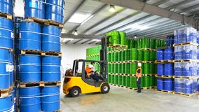 Group of workers in the logistics industry work in a warehouse w. Ith chemicals - lifting truck royalty free stock photography
