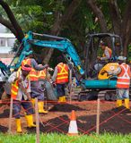 Group of workers in park. Singapore. SINGAPORE - JAN 16, 2017: Workers work in public park in Singapore. Singapore is a major political, financial, cultural hub Stock Photos