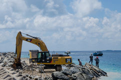 Group of workers using excavator at construction site on shore of ocean Royalty Free Stock Photography