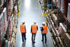 Group of Workers in Warehouse. Group of warehouse workers wearing hardhats and reflective jackets waking in aisle between tall racks with packed goods, back view stock images