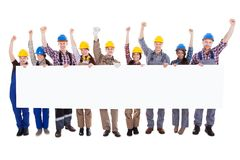 Group of workmen holding a blank white banner. Group of diverse skilled motivated workmen and women standing in a line cheering celebrating a success holding a Royalty Free Stock Photo