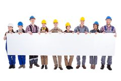 Group of workmen and women with a banner. Large diverse multiethnic group of workmen and women standing in a line holding a long blank white banner with Royalty Free Stock Image