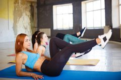 Women doing abdominal crunches at workout Stock Photos