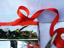Someone is preparing to wrap a gift box. A group of wrapped gift boxes for someone special in greeting moments. They're decorating with red satin ribbon. For stock images