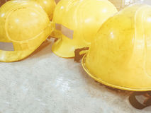 Group of yellow dirty safety helmet on white wooden table textur Royalty Free Stock Photography