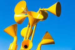 Group of yellow loudspeakers. Group of bright yellow loudspeakers over blue sky background, close up royalty free stock images