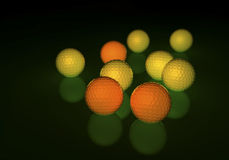 Group of yellow and orange golf balls, glowing on a reflecting surface Royalty Free Stock Images