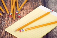 Group of yellow pencils and notepad on vintage wooden desk Stock Image
