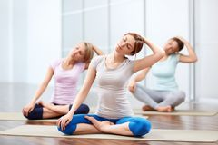 Group yoga sessions. Young girls do yoga indoors Stock Image