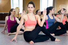 Group of yogi females in Ardha Matsyendrasana pose Stock Photography