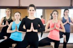 Group of yogi females doing Yoga practice. Sporty yogi girls in class in Yoga pose vrikshasana (Vriksasana or Tree Pose) using namaste Stock Images