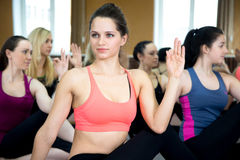 Group of yogi females in yoga pose Ardha Matsyendrasana Stock Image