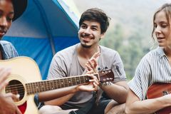 Group of young adult friends in camp site playing guitar royalty free stock photography