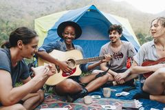 Group of young adult friends in camp site playing guitar stock photo