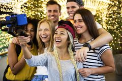 Group of young adult friends taking a group selfie with a selfie. Stick royalty free stock images