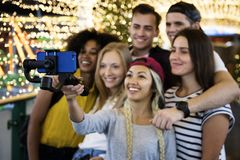 Group of young adult friends taking a group selfie with a selfie. Stick royalty free stock photography