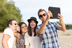 Group Of Young Adult Friends Taking Selfie. Young adult friends taking selfies with tablet and having fun outdoors royalty free stock photos