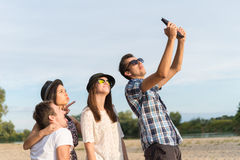 Group Of Young Adult Friends Taking Selfie. Young adult friends taking selfies with tablet and having fun outdoors royalty free stock photography