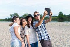 Group Of Young Adult Friends Taking Selfie. Young adult friends taking selfies with tablet and having fun outdoors royalty free stock images