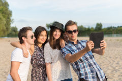 Group Of Young Adult Friends Taking Selfie. Young adult friends taking selfies with tablet and having fun outdoors stock images